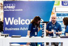 "Photograph of people at a booth in front of a partially obscured sign that says ""Welcome Business Advisors"""