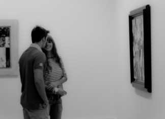 Black and white photograph of a couple in an art gallery, standing in front of a picture, the woman is laughing