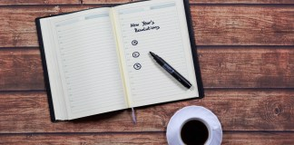 "Photograph of an open notebook with a pen on it; written on the notebook is ""New Years Resolutions"""