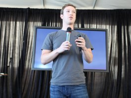 Photograph of Mark Zuckerberg standing with a microphone