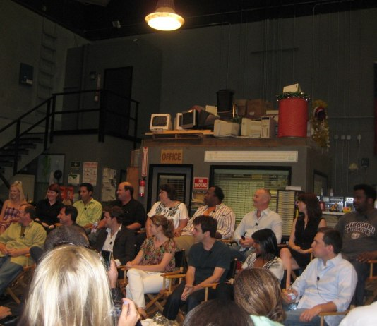 Photograph of the cast of the TV show The Office all sitting for a press conference on set