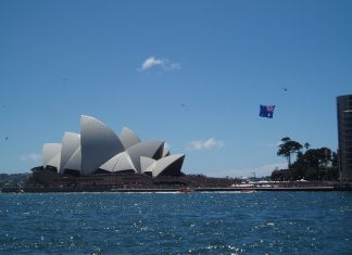 Photo of the Sydney Harbor overlooking the Opera House and an Australian flag flying in the sky from a plane