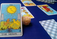 Photograph of the Moon tarot card propped against a crystal with several other tarot cards arranged in the background