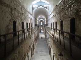 Photograph of a long hall of cells with light and a dome at the end