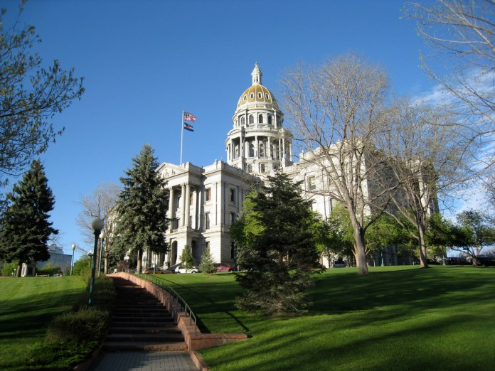 A photograph of the Colorado Capitol Building in Denver, with green grass and blue sky