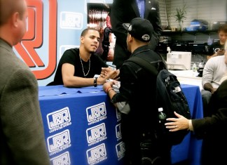 J. Cole sitting at a signing table shaking the hand of a fan