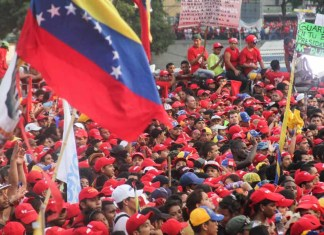 Photograph of a Venezuelan flag in the foreground and a crowd of protesting people in the background