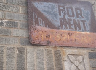 A rusted red sign that says For Rent