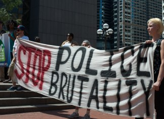 """Photograph of protesters holding """"Stop Police Brutality"""" banner"""
