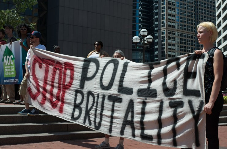 "Photograph of protesters holding ""Stop Police Brutality"" banner"