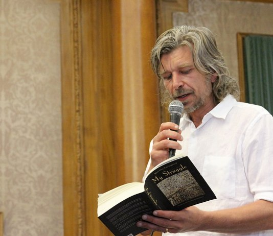 """Photograph of author Karl Ove Knausgard standing, holding a microphone, and reading from a book where the title """"My Struggle"""" is visible"""