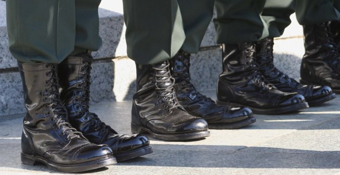 close-up photograph of the boots of four servicepeople