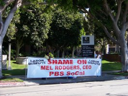 """Photo of a person behind a banner that says """"Shame on Mel Rogers, CEO, PBS SoCal"""""""