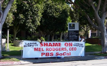 "Photo of a person behind a banner that says ""Shame on Mel Rogers, CEO, PBS SoCal"""