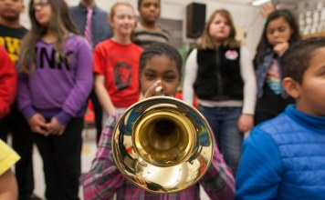 photograph of a girl playing the trumpet in a group of young students