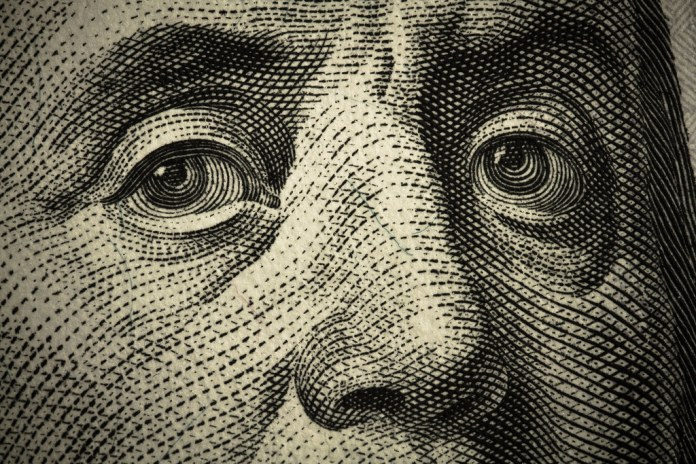 closeup photograph of Ben Franklin's face on $100 bill