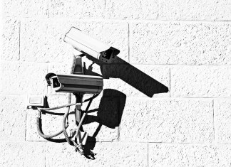 photograph of two security cameras on side of building