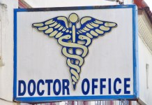 photograph of doctor's shingle with caduceus image