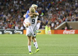 photograph of two female soccer plays celebrating during match