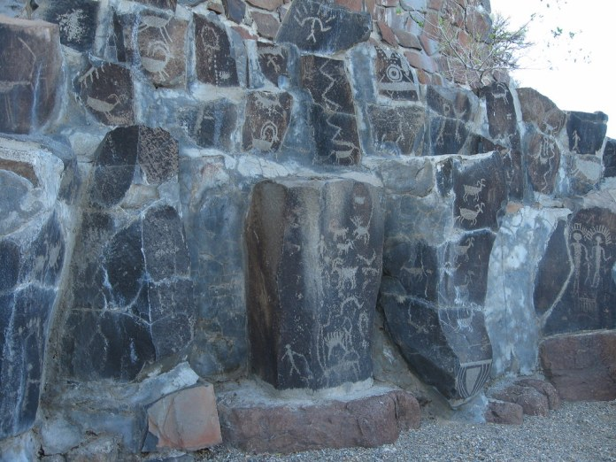 photograph of petroglyphs etched in a number of different stone faces