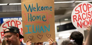 """photograph of """"Welcome Home Ilhan"""" sign held by supporter with others gathered at MSP"""