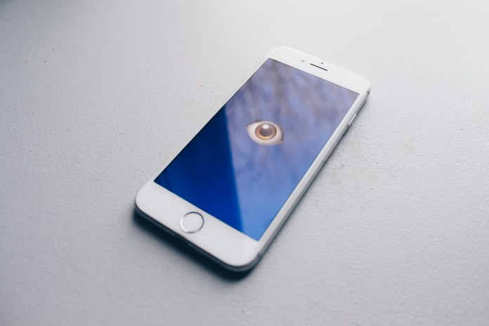 photograph of iphone with image of an eye on screen