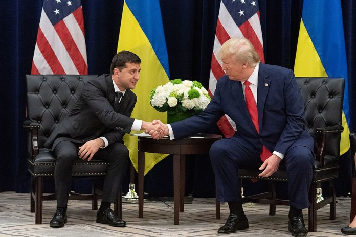 photograph of Trump and Zelensky posing for cameras, seated and shaking hands