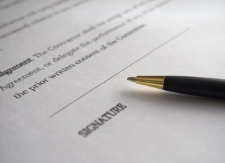 """close-up photograph of contract with pen laying on """"signature"""" section"""