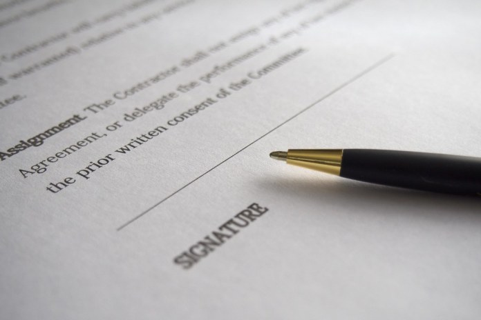close-up photograph of contract with pen laying on