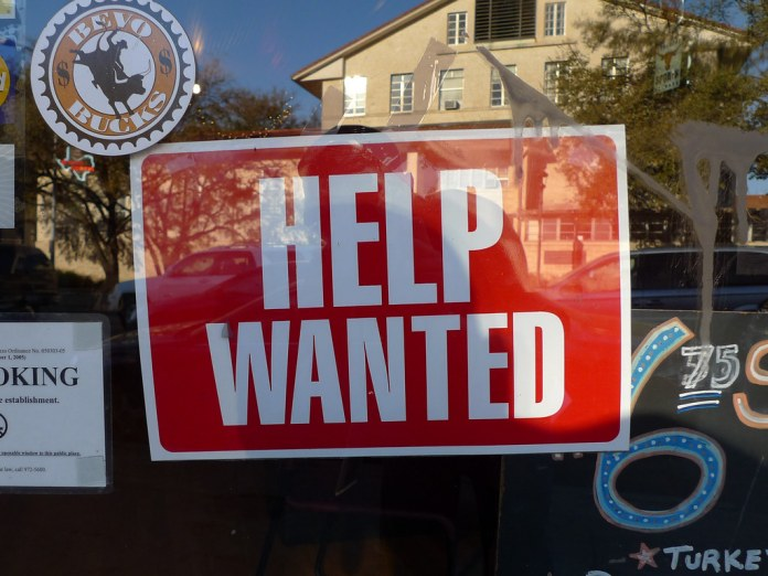 close-up photograph of 'Help Wanted' sign in storefront window
