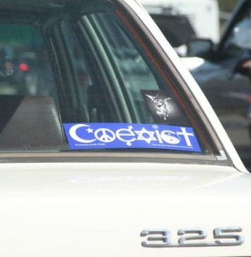 "photograph of ""Coexist"" bumper sticker in back window of a BMW"