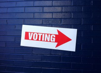 """photograph of """"voting"""" sign on a wall"""