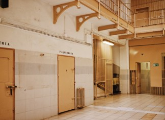 Yellow and white corridor with metallic doors of cell rooms in old prison