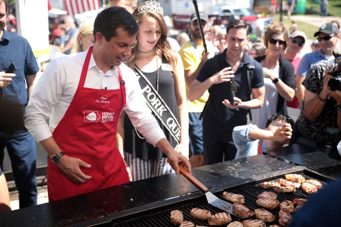 photograph of Mayor Pete at an even flipping pork chops in Iowa Pork apron