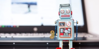 photograph of chat bot figurine in front of computer