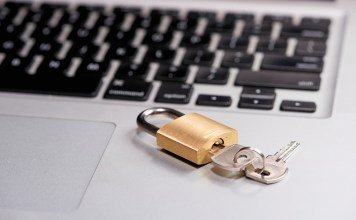 photograph of laptop with a lock with keys on it