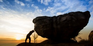 photograph of silhoutted man leaning against boulder at dawn