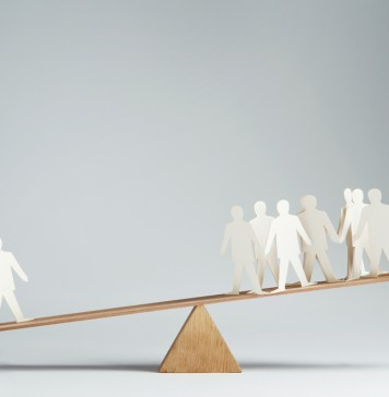photograph of seesaw with 1 paper cutout man balanced against 20