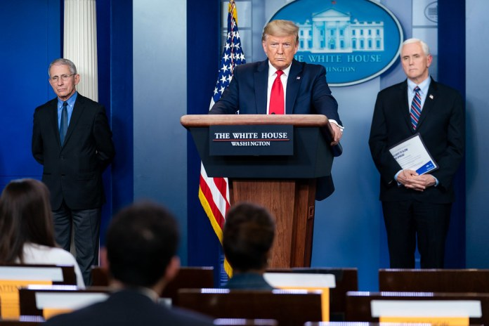 photograph of Trump answering questions at press briefing with Vice President Pence and Dr. Fauci one either side