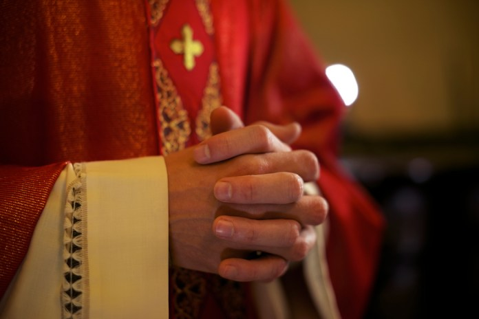 close-up photograph of catholic priests folded hands