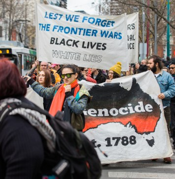 "Protest in Australia; two signs are visible: one reads ""lest we forget the frontier wars, black lives, white lies"" and one shows a black and red image of Australia with the word ""genocide"" written on it"