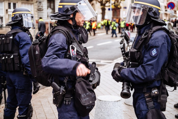 two police officers dressed in riot gear holding smoke grenade guns