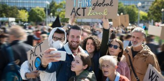 A group of six people holding signs at a protest, gathering to be included in a selfie taken with a phone