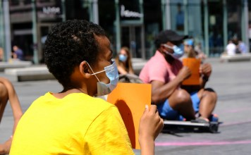 Young person sitting on cement wearing a mask and holding a sign, turned away from camera. More people also sitting and holding signs are visible in the background.