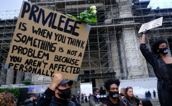 photograph of BLM protester with sign explaining white privilege