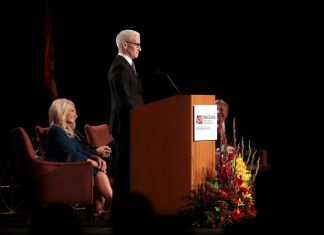 Anderson Cooper standing at a podium with a woman sitting in a chair behind him
