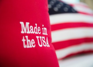 "photograph of ""Made in the USA"" embroidered pillow will US flag pillow in background"