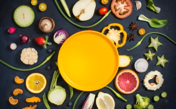 photograph of halved fruits and vegetables arranged around yellow plate in the center