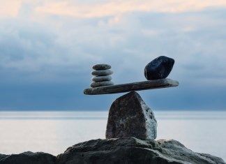 photograph of scales made of pebbles balanced on a boulder