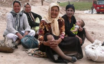 photograph of four Uighur women, one with a baby